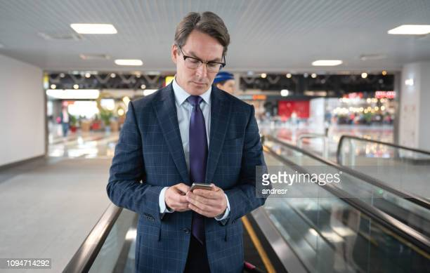 Traveling business man using cell phone on a moving walkway at the airport