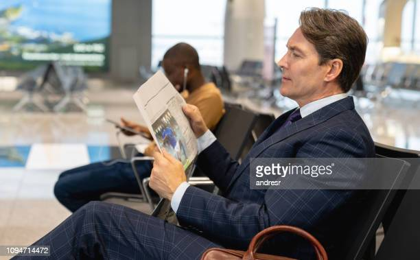 Traveling business man waiting by the gate at the airport and reading the newspaper