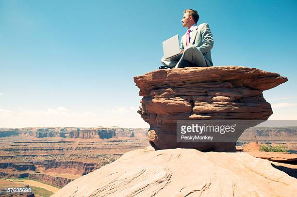 Traveling Businessman Sitting With Laptop on Rock Mesa