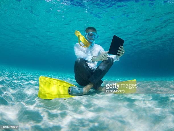 Traveling Businessman Using Digital Tablet Computer Underwater in Sea