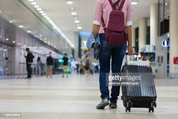 traveling concept. rear view of traveler walking with a luggage at airport terminal . - emigration and immigration stock pictures, royalty-free photos & images