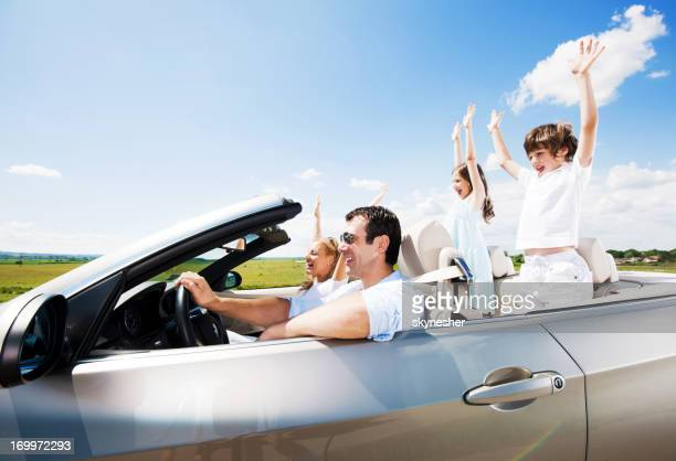 Traveling family driving in the Convertible car.