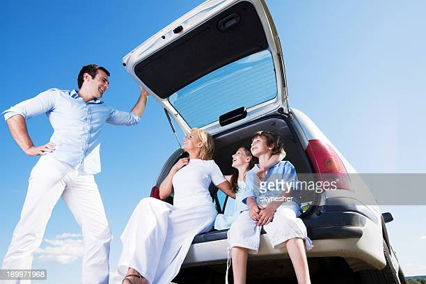 Traveling family sitting in a car trunk of minivan.