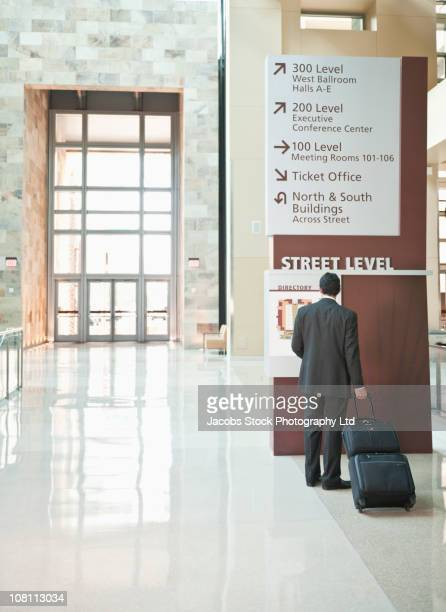 Traveling Hispanic businessman looking at building directory