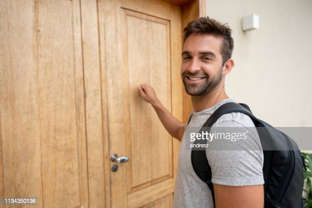 traveling man knocking on the door of a hostel - guest stock pictures, royalty-free photos & images