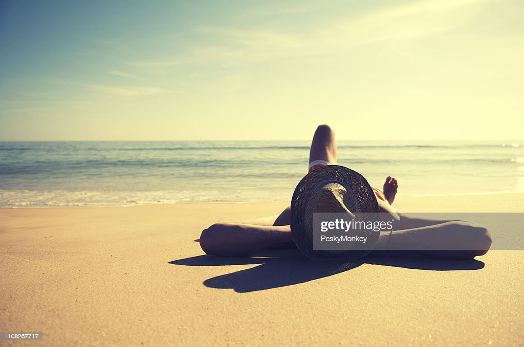 Traveling Man Relaxing on Tranquil Vintage Beach Wearing Hat : Stock Photo