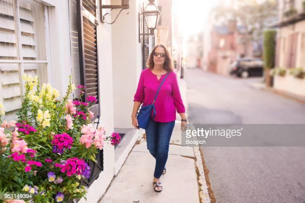 Traveling Senior Woman Walking on Sidewalk Charleston South Carolina USA