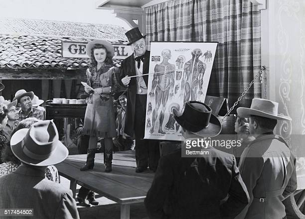 A traveling snakeoil salesman points to an illustration of the human body during a scene from the 1944 Republic Pictures' film Song of Nevada The...