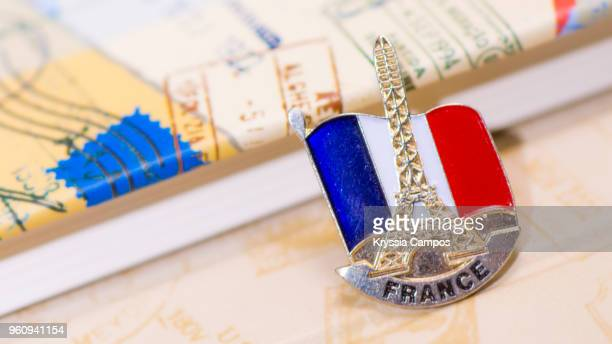 traveling souvenir: pin brooch from france - brooch stock-fotos und bilder