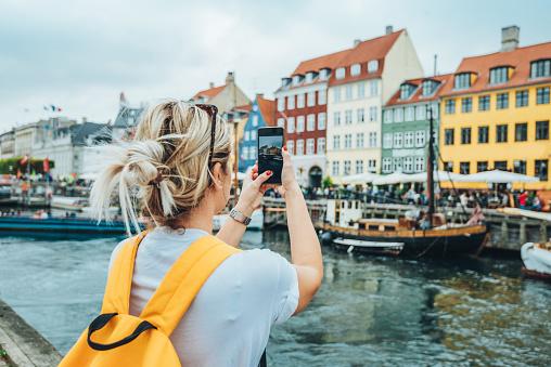 Traveling to Copenhagen - tourist in Nyhavn 1058837752