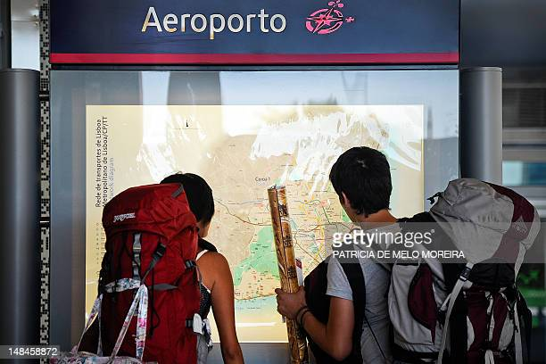 Traveling tourists consult a map at the Lisbon airport subway station on July 17 2012 Metro Lisbon inaugurated on July 16 three new subway stations...