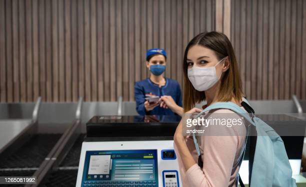 traveling woman doing the check-in at the airport wearing a facemask - biosecurity stock pictures, royalty-free photos & images