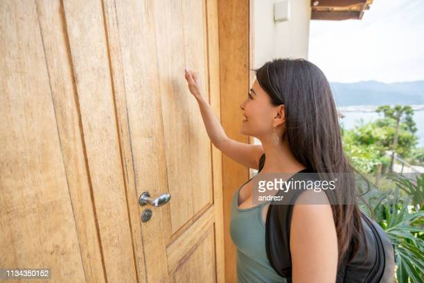 traveling woman knocking on the door of a lodging house - bella ciao foto e immagini stock