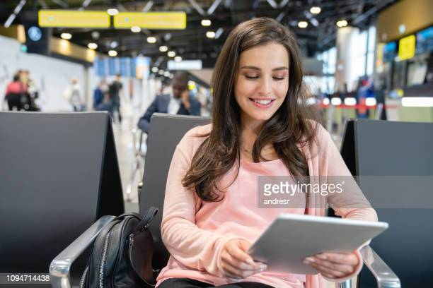Traveling woman waiting by the gate at the airport using a tablet computer