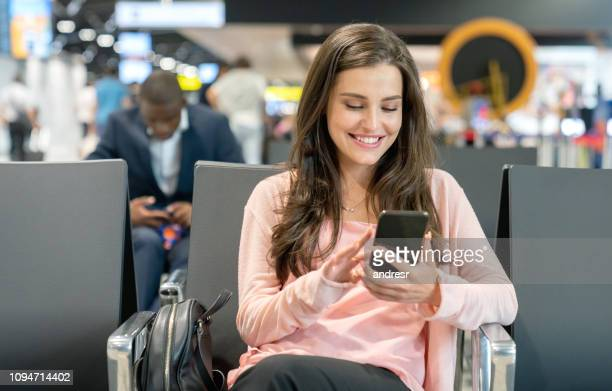 Traveling woman waiting by the gate at the airport using her cell phone