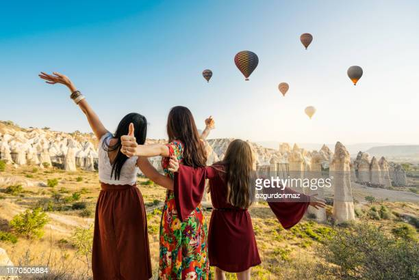 traveling women looking at air balloons in sky in cappadocia valley. - cappadocia stock pictures, royalty-free photos & images