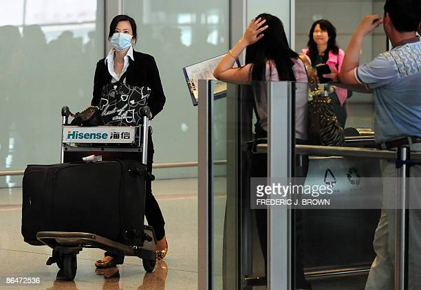 A traveller arrives wearing a protective facemask at Beijing airport on May 7 2009 as China started lifting a sevenday quarantine on passengers who...
