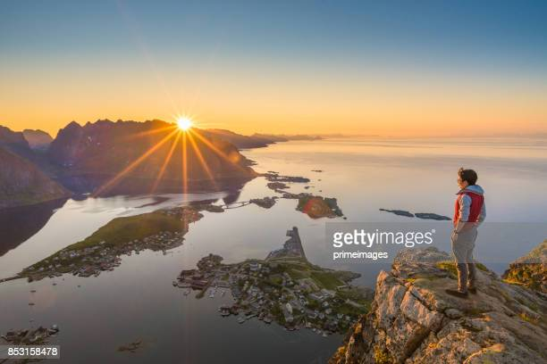 Traveller enjoy summer view of Lofoten Islands in Norway with sunset scenic