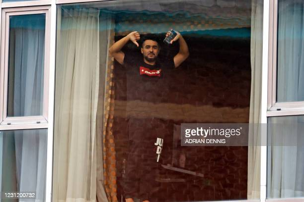 Traveller gestures as he look out of a window during mandatory hotel quarantine in a Radisson Blu hotel at Heathrow Airport in west London on...