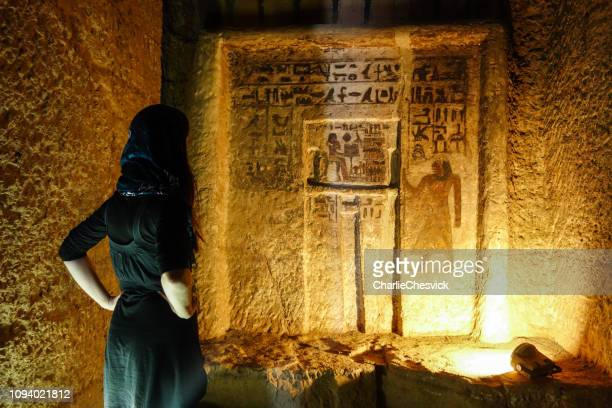 traveller inside tombs of the nobles, ruins from old kingdom in asuán - tomb stock pictures, royalty-free photos & images