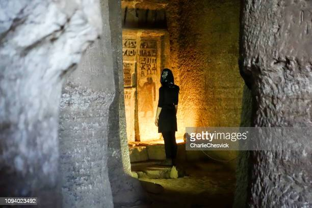 traveller inside tombs of the nobles, ruins from old kingdom in asuán reading hieroglyphs - antico egitto foto e immagini stock