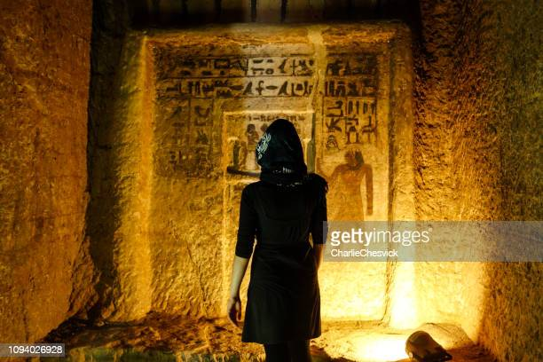traveller inside tombs of the nobles, ruins from old kingdom in asuán reading hieroglyphs - ancient egyptian culture stock photos and pictures