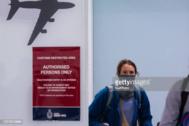 A traveller is seen covering her face as the coronavirus continues to spread across Australia on March 20 2020 in Melbourne Australia Earlier Prime...