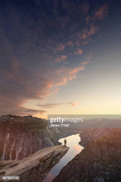 traveller looking out at landscape at sunset, trolltunga, norway - hordaland county stock pictures, royalty-free photos & images