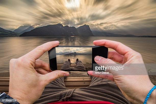 Traveller man taking pictures with smartphone from personal point of view of his legs laying in front of the Swiss lake with sunset light.