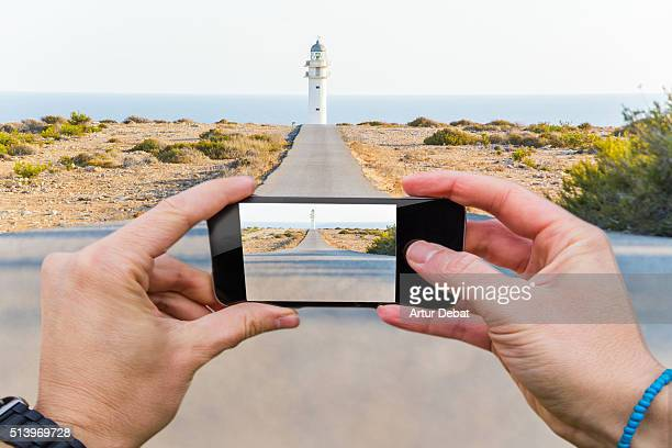 Traveller man taking pictures with smartphone from personal point of view of the Formentera island landscape with straight road and lighthouse.