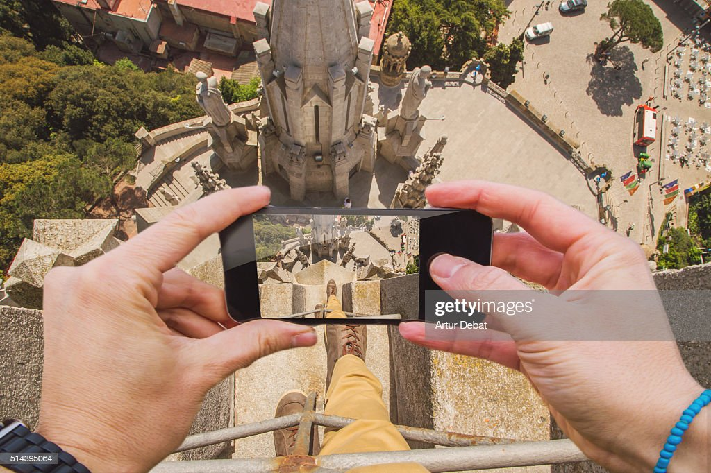Traveller man taking pictures with smartphone from personal point of view of his legs on top of the Tibidabo church in Barcelona looking down. : Stock Photo
