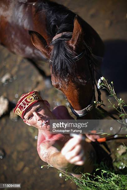 A traveller named Jackie reaches for a cigarette whilst washing his horse in the River Eden in preparation for selling at the Appleby Horse Fair on...