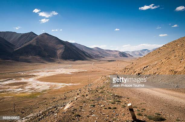 A traveller on a journey around the world by bicycle is watching the scenery of the Pamirs of Tajikistan after cycling up to Ak-Baital pass (4655m)