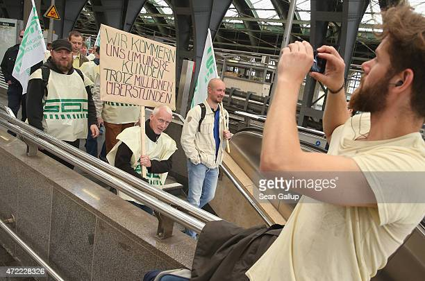 A traveller photographs striking members of the GDL train drivers' union as they stroll through Ostbahnhof train station on the first full day of...
