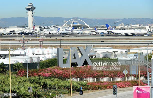 A traveller pulls his bags while walking past an LAX sign at Los Angeles International Airport as access roads were closed with flights delayed and...