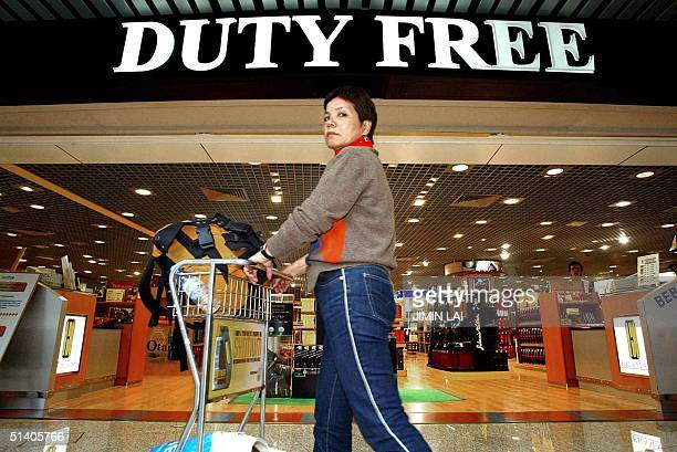 Traveller pushes her trolley past a duty free shop at the shopping concourse of the KL International Airport in Sepang, 10 October 2002. KLIA has...