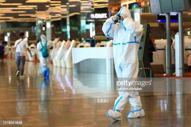 Traveller puts on the personal protective equipment before checking-in at Changi Airport on June 10, 2020 in Singapore. Singapore begins to gradually...
