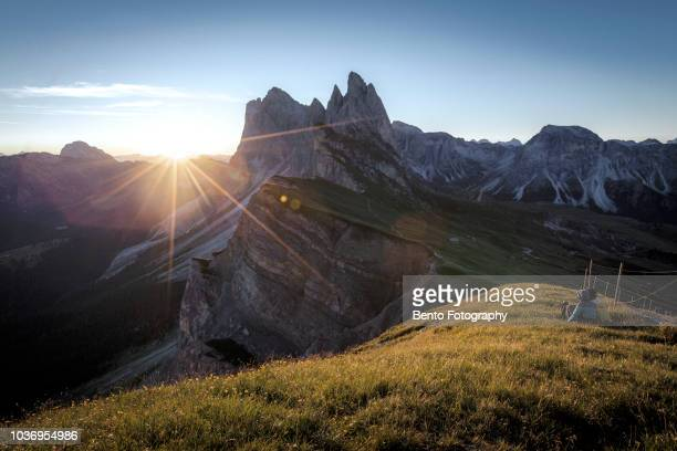Traveller sitting on the grass looking for sunrise in Seceda, Dolomite, Italy