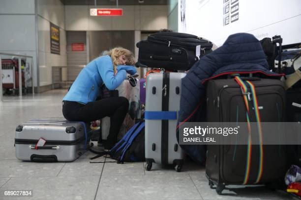 A traveller sleeps next to luggage at Heathrow Airport Terminal 5 after British Airways flights where cancelled at Heathrow Airport in west London on...