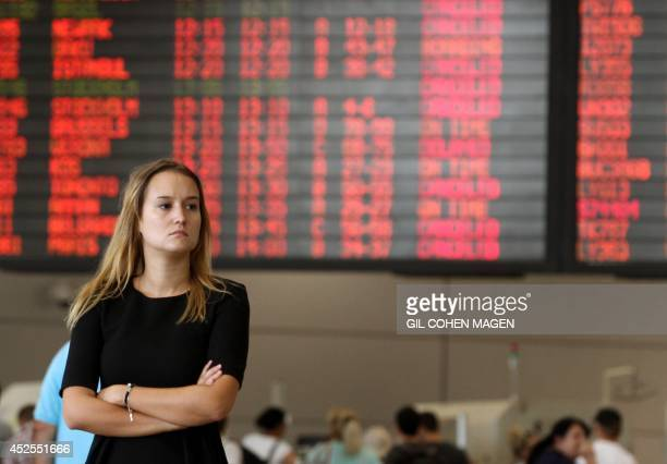 A traveller stands in front of a departure time flight board displaying various cancellations at Ben Gurion International airport near Tel Aviv on...