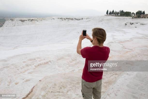 Traveller takes photo of white travertine terraces