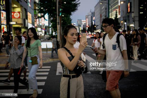 A traveller takes selfies at the Shinjuku in Tokyo Tokyo is Japan's capital and one of the world's most populous metropolis