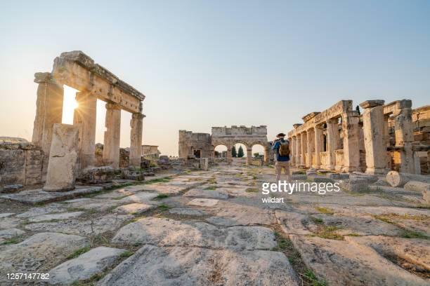 reisender tourist macht foto von frontinus tor in alten ruinen in hierapolis, pamukkale - geschichtlich stock-fotos und bilder