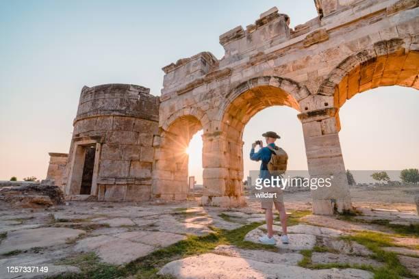 touriste de voyageur prend la photo de la porte de frontinus dans les ruines antiques à hierapolis au coucher du soleil , pamukkale - athènes photos et images de collection