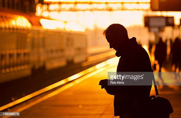 Traveller using phone while waiting for train