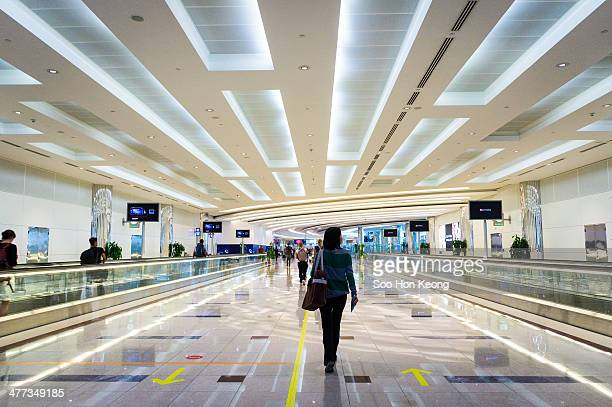 Traveller walking through Dubai International Airport. The airport is one of the major transit point to Europe for southeast asia travellers