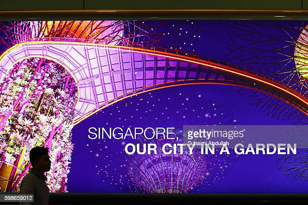 A traveller walks past a giant billboard at the Changi International Airport on August 26 2016 in Singapore