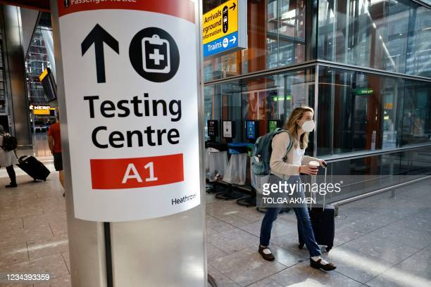 Traveller walks past a sign directing the public to a Covid testing centre at Terminal 5 in west London on August 2, 2021 as quarantine restrictions...