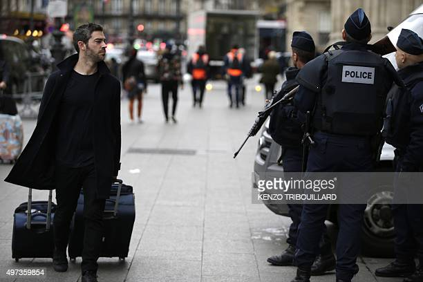 A traveller walks past policemen standing guard outside the Gare du Nord railway station on November 16 2015 in Paris three days after the terrorist...