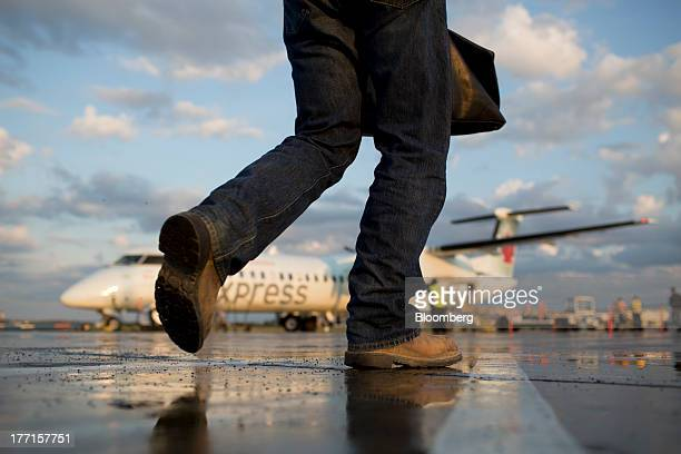 A traveller walks to an Air Canada Express aircraft at the Fort McMurray airport in Fort McMurray Alberta Canada on Tuesday Aug 13 2013 Canadian oil...